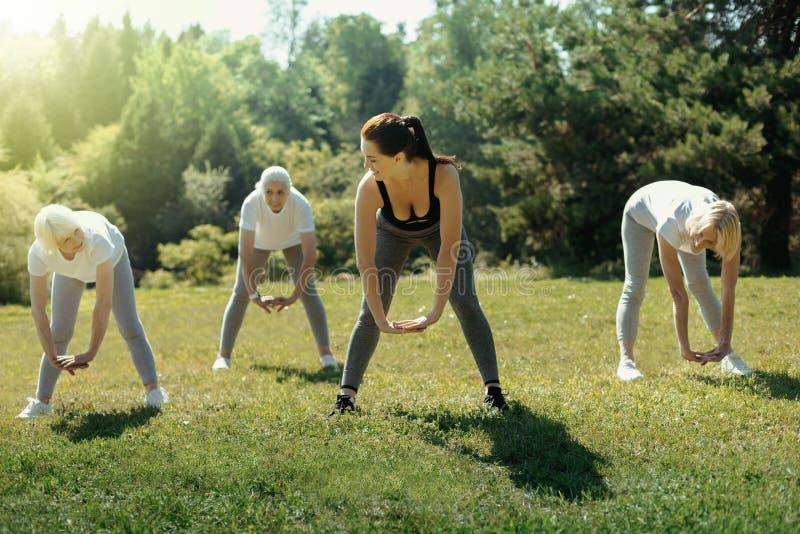 Bejaarde dames die ruggen uitrekken tijdens groepstraining stock afbeelding