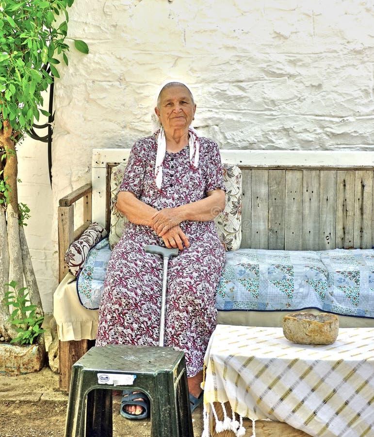 Bejaarde damezitting in haar tuin stock foto's