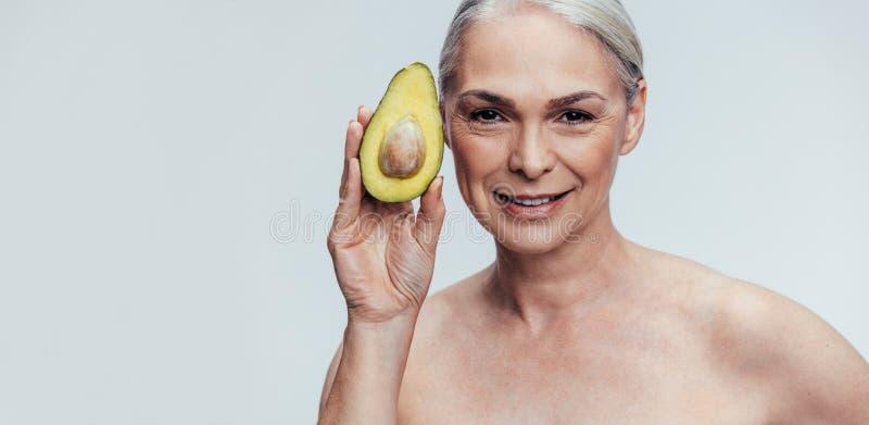 Bejaarde dat een avocado toont stock afbeeldingen