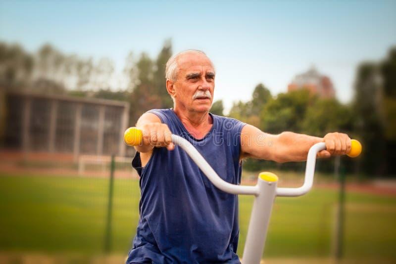 Bejaarde dat in geschiktheidsgymnastiek uitwerkt stock foto