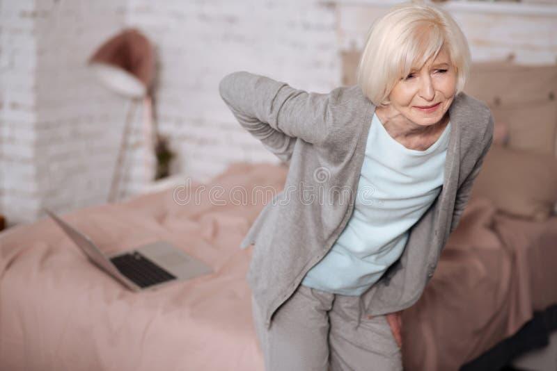 Bejaarde dat zich met rugpijn bevindt stock foto's