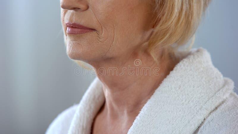 Bejaarde de status in badrobe en het kijken in spiegel, lichaamsverzorging, sluiten omhoog stock afbeeldingen