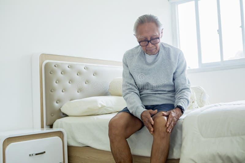 Bejaarde die aan kniepijn thuis lijden stock afbeelding