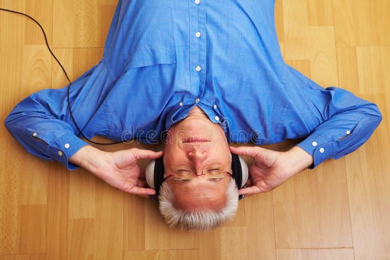 Bejaarde die aan muziek luistert royalty-vrije stock afbeelding