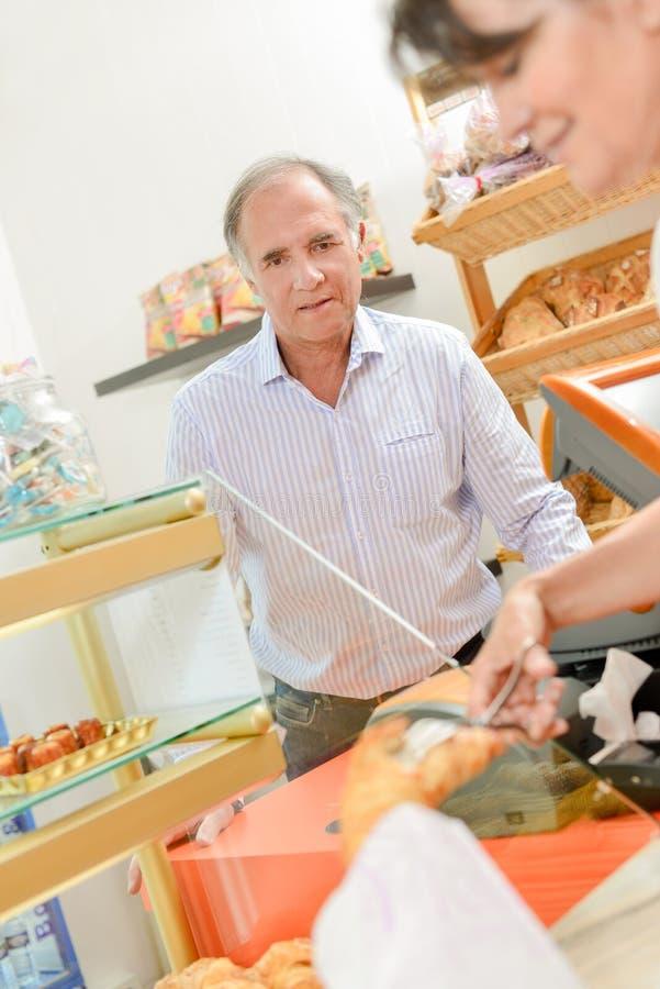 Bejaarde die in bakkerij worden gediend stock foto
