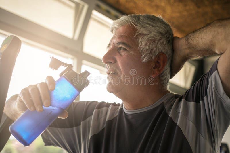 Bejaarde die een fles water houden De man wordt verfrist stock fotografie