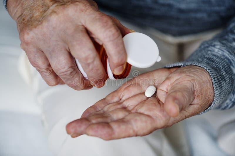 Bejaarde die een geneeskunde nemen stock foto