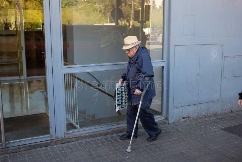 Bejaarde die een hoed dragen en één het lopen hulp gebruiken royalty-vrije stock afbeeldingen