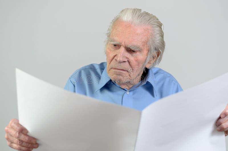Bejaarde die een leeg groot Witboekblad houden stock afbeeldingen