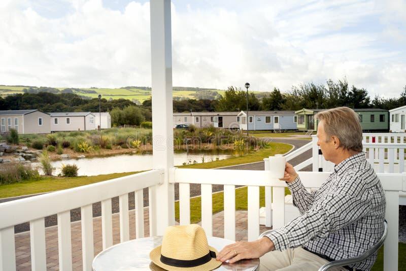Bejaarde die een mok van koffiezitting drinken op de veranda van a stock foto