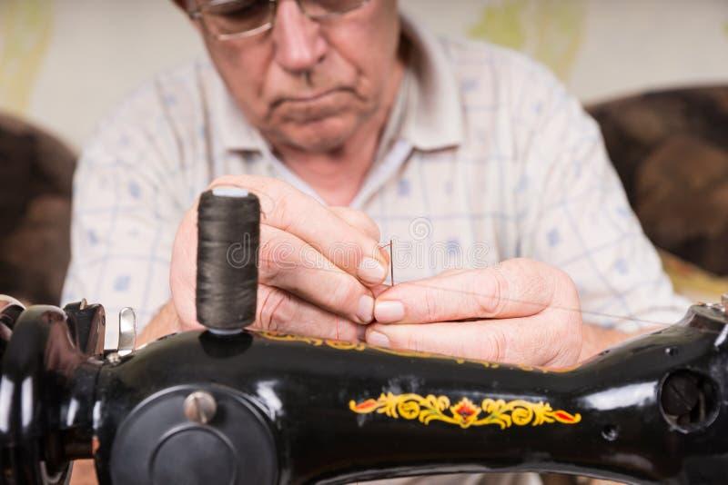 Bejaarde die een naald met garen inpassen stock foto