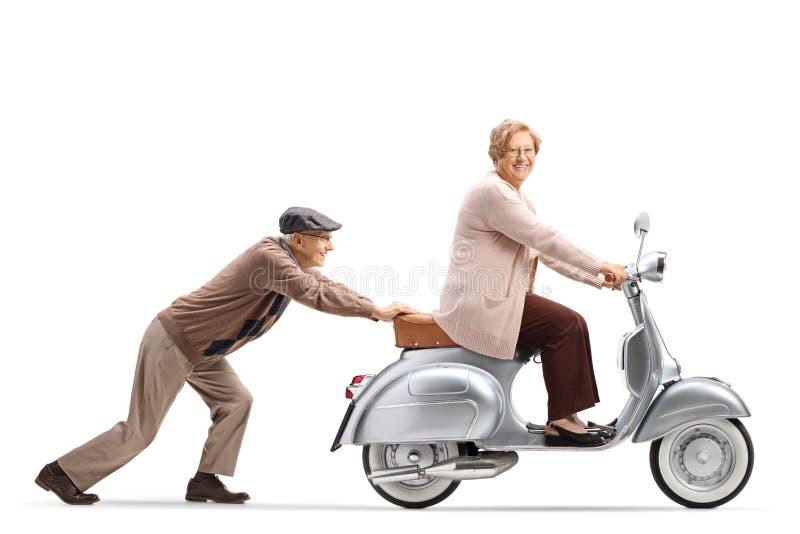 Bejaarde die een bejaarde op een uitstekende motor duwen royalty-vrije stock foto's