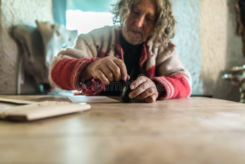 Bejaarde die een pot van inkt gebruiken om kalligrafie te doen stock afbeeldingen