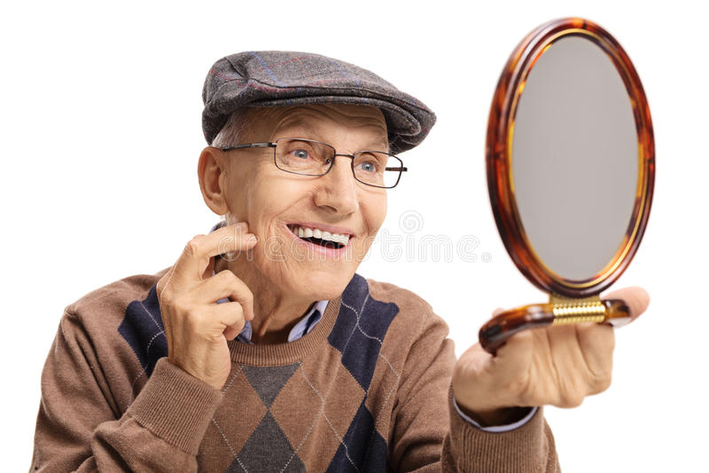 Bejaarde die een spiegel en het glimlachen bekijken royalty-vrije stock fotografie