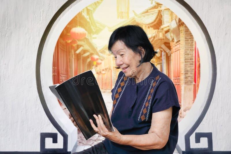 Bejaarde die een tijdschrift in Chinese oldtown lezen royalty-vrije stock fotografie