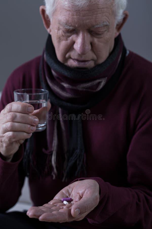 Bejaarde die geneeskunde neemt stock fotografie