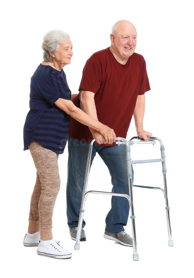 Bejaarde die haar echtgenoot met het lopen kader helpen stock foto's