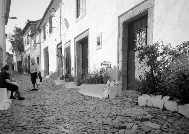 Bejaarde die haar vrienden in een straat in Portugal ontmoeten royalty-vrije stock foto's