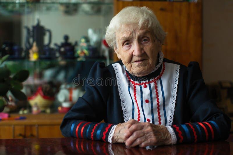 Bejaarde die in heldere kleren bij de lijst zitten Portret royalty-vrije stock foto's