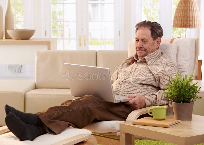 Bejaarde die laptop computer met behulp van stock afbeeldingen