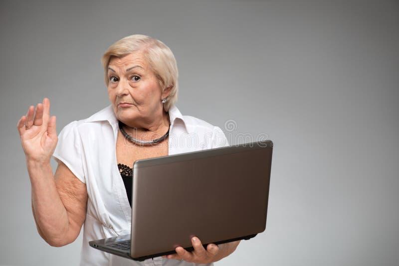 Bejaarde die laptop houden stock foto
