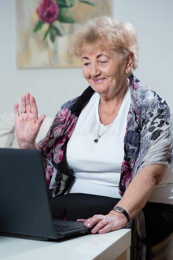 Bejaarde die online spreken stock fotografie