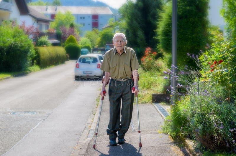 Bejaarde die op steunpilaren op een stoep lopen stock foto