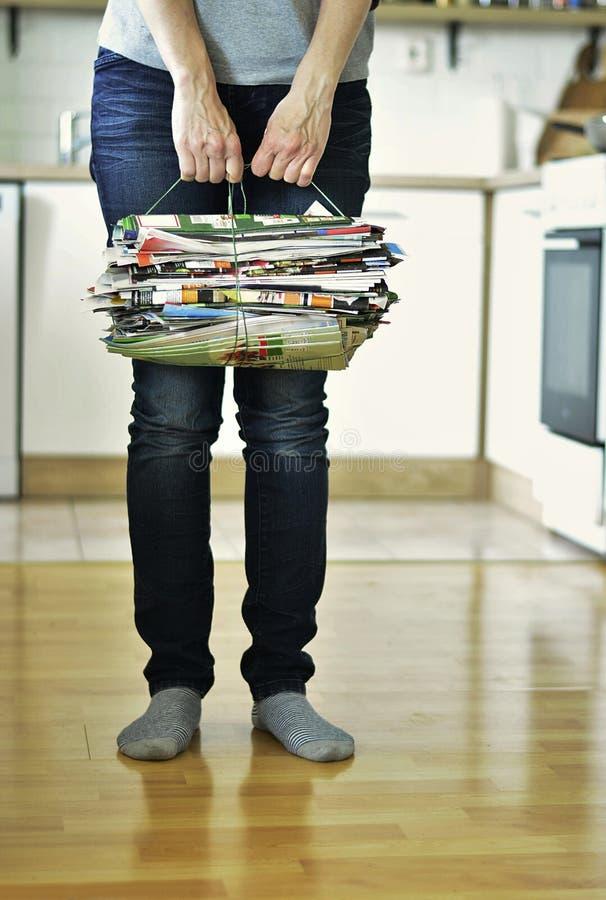 Bejaarde die oude tijdschriften voor thuis recycling houden stock foto