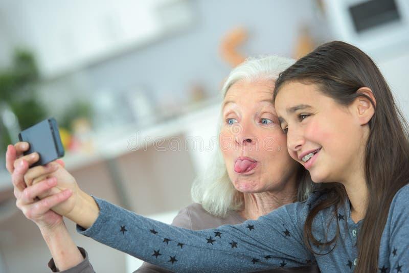 Bejaarde die selfie met jonge kleindochter thuis maken royalty-vrije stock afbeelding