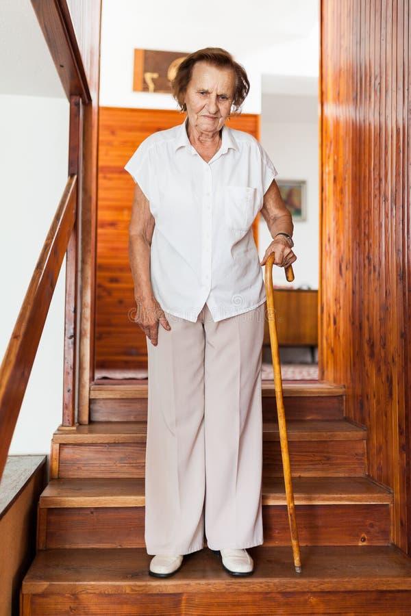 Bejaarde die thuis een riet onderaan de treden gebruiken te krijgen royalty-vrije stock foto's