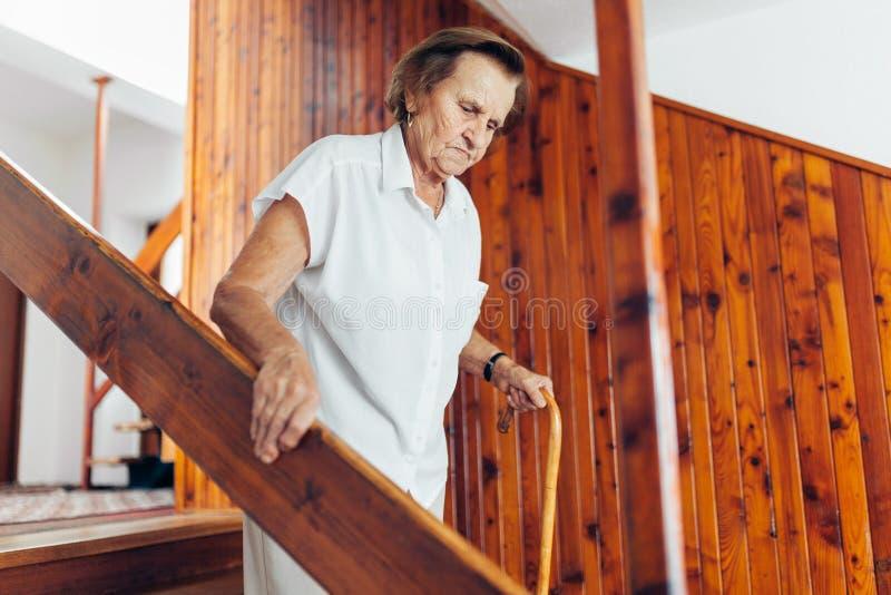 Bejaarde die thuis een riet onderaan de treden gebruiken te krijgen stock foto