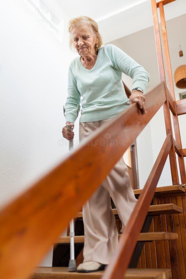 Bejaarde die thuis een riet onderaan de treden gebruiken te krijgen royalty-vrije stock afbeelding
