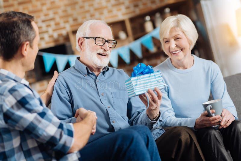 Bejaarde die verjaardagsgeschenk van zijn familie bekijken royalty-vrije stock afbeeldingen