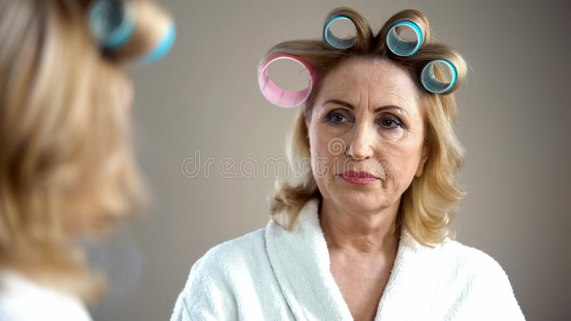 Bejaarde die die voor partij voorbereidingen treffen, met haar gedachtengang in spiegel wordt teleurgesteld royalty-vrije stock foto