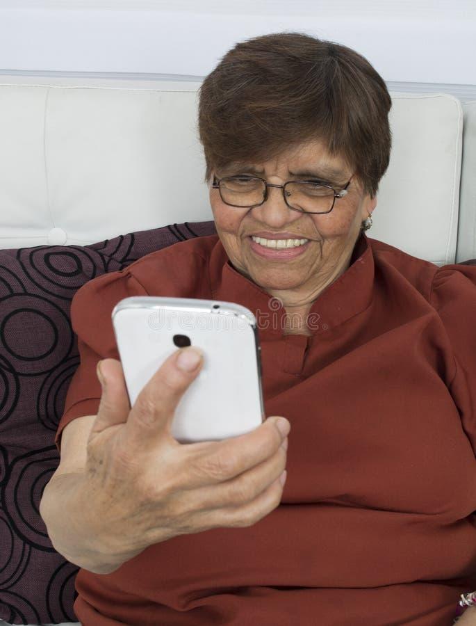 Bejaarde die zelf-foto's, selfies op haar slimme telefoon maken stock fotografie