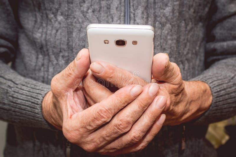 Bejaarde die zich met mobiele in hand telefoon bevinden royalty-vrije stock afbeelding