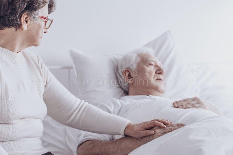 Bejaarde die zieke echtgenoot bezoeken stock foto's