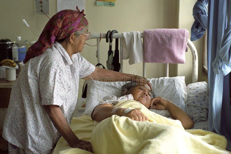 Bejaarde die zieke zuster in het ziekenhuis troosten royalty-vrije stock afbeelding