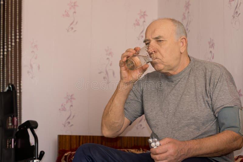 Bejaarde die zijn medicijn nemen stock afbeeldingen
