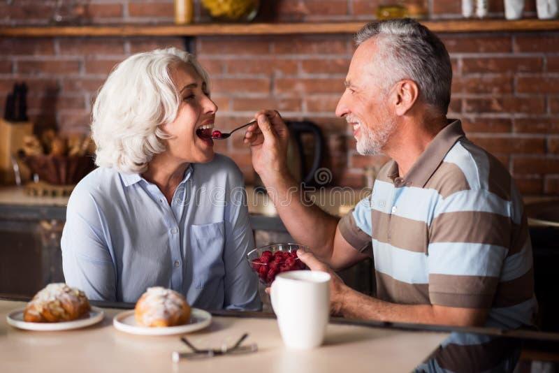 Bejaarde die zijn mooie vrouw voeden stock afbeelding