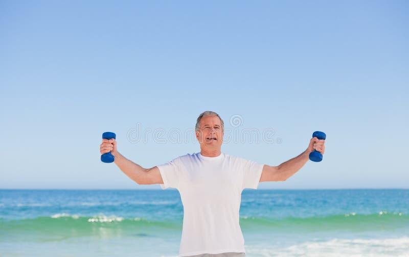 Bejaarde die zijn oefeningen doet stock foto