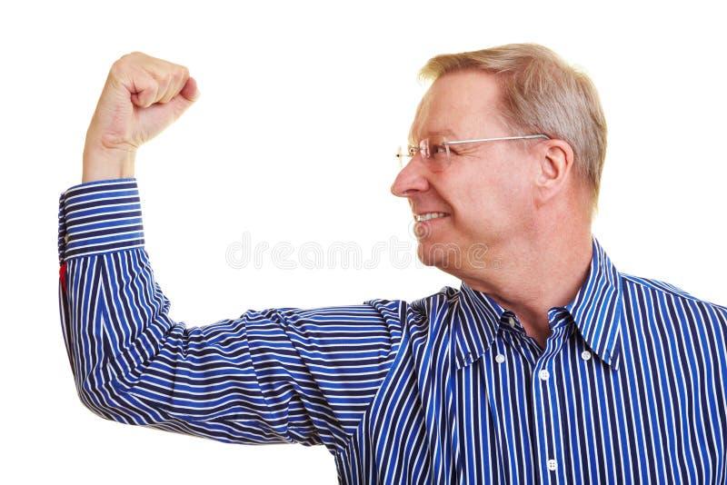 Bejaarde die zijn spieren buigt stock foto's