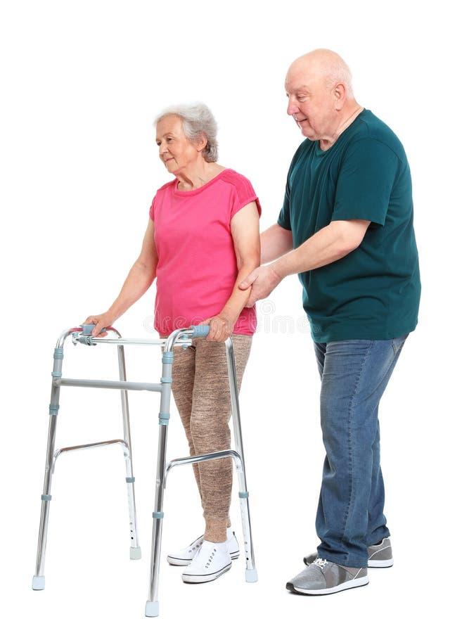 Bejaarde die zijn vrouw met het lopen kader op wit helpen royalty-vrije stock foto
