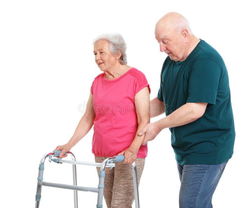 Bejaarde die zijn vrouw met het lopen op witte achtergrond helpen royalty-vrije stock foto