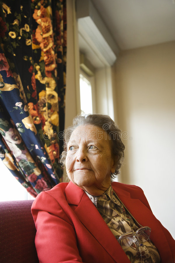 Bejaarde door venster. royalty-vrije stock afbeelding