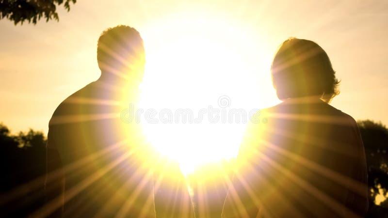 Bejaarde echtgenoot en vrouwenschaduwen in zonsondergangverlichting, het ontspannen park samen stock afbeelding