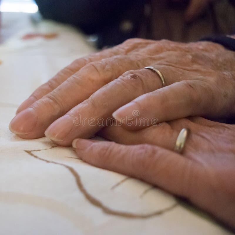 Bejaarde echtpaarhanden met trouwringen royalty-vrije stock afbeelding