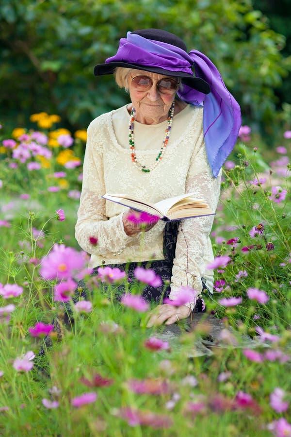 Bejaarde in een de zittingslezing van de beautitulhoed stock foto