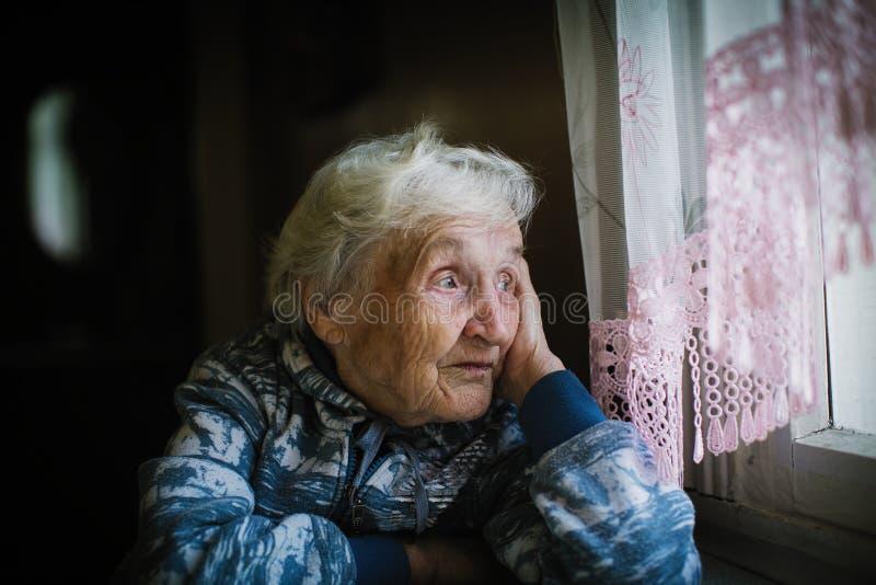 Bejaarde eenzame vrouw in de huiszitting bij de lijst die uit het venster kijken stock foto's