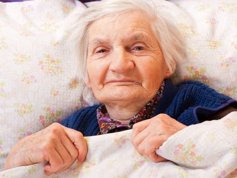 Bejaarde eenzame vrouwenrust in het bed royalty-vrije stock afbeelding
